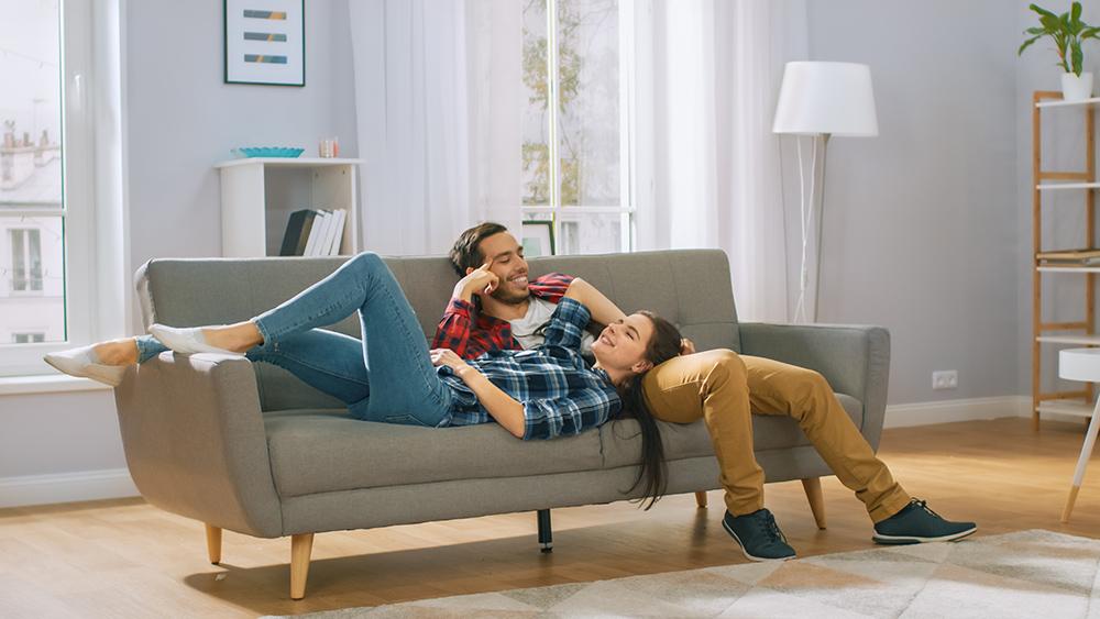 Couple relaxing on grey sofa