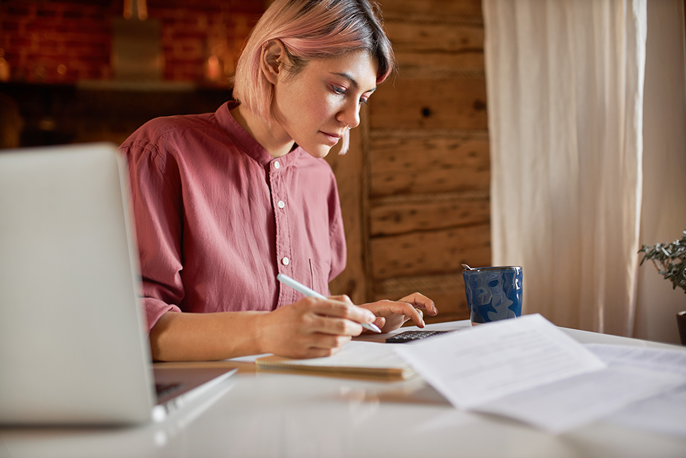 Women with pink hair working from home at desk with laptop and calculator