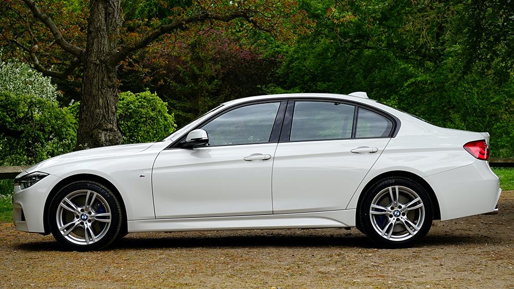 White BMW car next to woodland