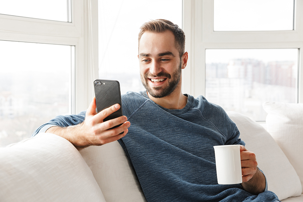 Young man sitting on white sofa. Wearing blue sweater. Holding white mug and mobile phone