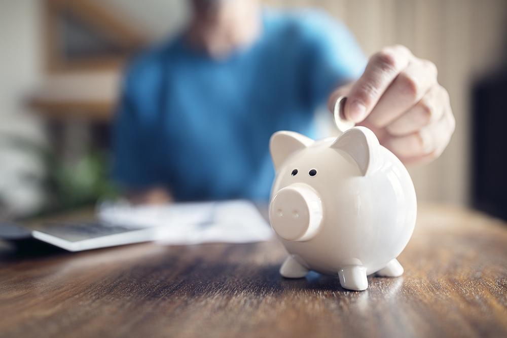 Person putting money into a white piggy bank - savings