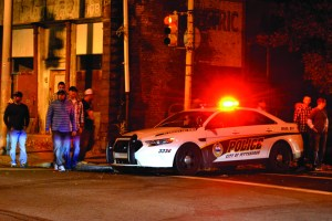 "Photo by Taylor Miles | The Duquesne Duke. A Pittsburgh Police car flashes its lights on Saturday night in South Side. Since ""saturation detail"" was instituted, crime and 911 calls have decreased, according to police."