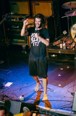 Dan Lambton of Real Friends shouts and points to the audience during his set.