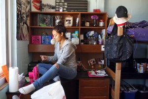 Somer Gaines, left, a first generation college student, puts the finishing touches on her dorm room at the University of Nebraska-Lincoln by hanging up a Marilyn Monroe poster in Smith Hall Dormitory on Monday, Aug. 24, 2015 in Lincoln, Neb. Somer participated in a new orientation program for first generation student prior to the star of school. (Jenna Vonhofe/Lincoln Journal Star via AP)