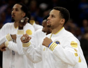 Golden State Warriors' Stephen Curry, right, wears his championship ring during an awards ceremony prior to the NBA basketball game against the New Orleans Pelicans Tuesday, Oct. 27, 2015, in Oakland, Calif. (AP Photo/Ben Margot)
