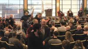 Screenshot taken from the live footage of the event provided by Duquesne Media Services Four protesters are escorted out of the Duquesne Power Center Ballroom by police after protesting against General Michael Hayden, who was giving a speech on campus Tuesday afternoon.