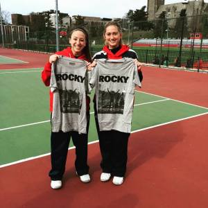 "Courtesy of the Duquesne Duke - Julianne Herman (right) and teammate Kylie Isaacs (left) hold up t-shirts depicting a famous scene from the movie ""Rocky,"" of which they are big fans."