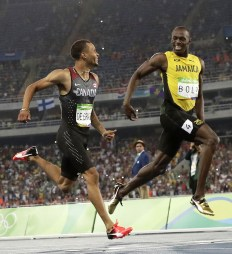 FILE - In this Aug. 17, 2016 file photo, Canada's Andre De Grasse, left, and Jamaica's Usain Bolt smile at each other in a men's 200-meter semifinal, during the athletics competitions of the 2016 Summer Olympics at the Olympic stadium in Rio de Janeiro, Brazil. Bolt is leaving, and insists he's never coming back. The departure of the sport's most electric athlete from the Olympics certainly makes the Tokyo Games feel like a less-enticing prospect. Somebody will have to take center stage in the marquee events, the men's sprints. The early candidate is de Grasse. (AP Photo/Matt Dunham, File)