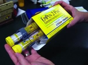 A pharmacist holds a package of EpiPens. The life-saving drug was victim to a massive price increase that made it difficult for many who needed it to actually attain.