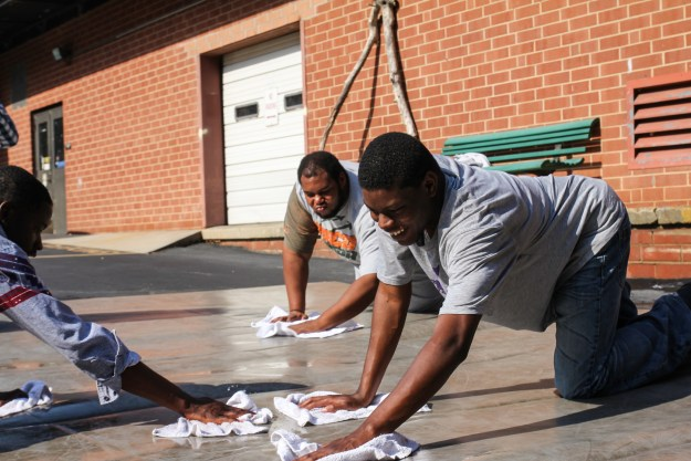Aikido club members washing the mats donated from the Basic Law Enforcement Training program