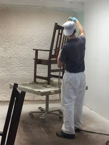 Applying stain in the prep area at Schlabach Finishing Shop.