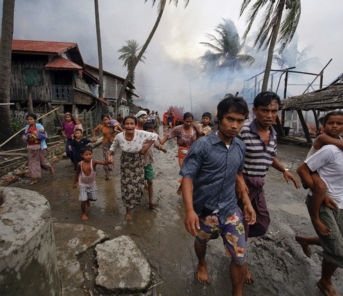 Rohingyas run away from a fire that was set to a part of Sittwe, during clashes