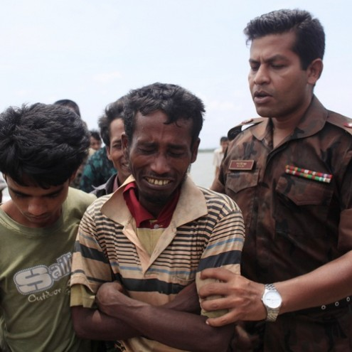 A member of Border Guards of Bangladesh (BGB) comforts a Rohingya from Myamar after being arrested while trying to get into Bangladesh, in Teknaf