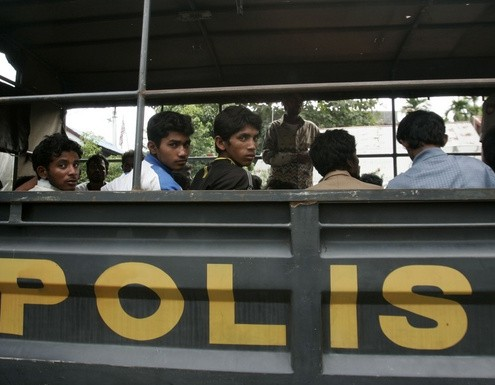 Ethnic Rohingya people from Myanmar wait inside a police truck for identification by immigration personnel in Lhokseumawe