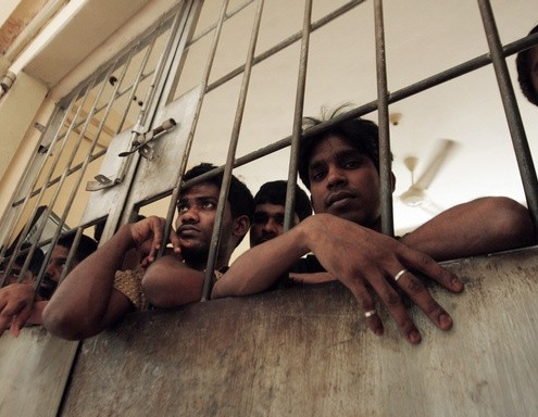 Illegal migrants from Myanmar stand at the gate of an immigration detention centre in Medan in Indonesia's North Sumatra province