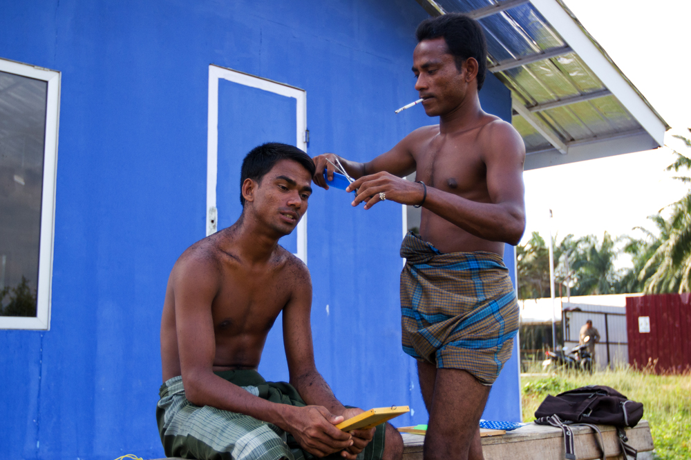 A Rohingya refugee gives another a haircut at Bayeun Refugee Camp, in the outskirts of Langsa City (Aceh Province, Indonesia). Photo: Carlos Sardiña Galache / Yayasan Geutanyoe – A Foundation for Aceh.