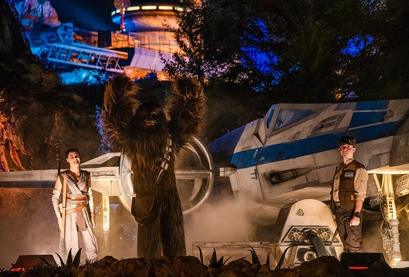 Star Wars Galaxy's Edge cast, Chewbacca, Ray, and Rebel Soldier in front of a blue X-Wing Fighter