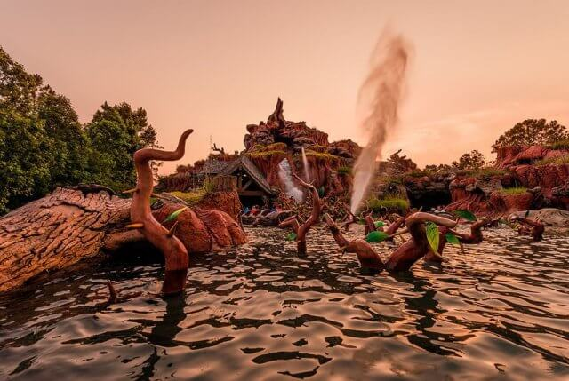 A view of splash mountain at the magic kingdom from the water with water spraying in the air.