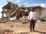 man next to destroyed house