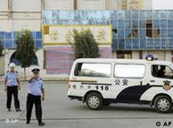 Police pointing at a photographer taking photos of the attack site in Kashgar.