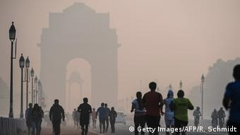 Indian joggers exercise on a smoggy morning near the India Gate monument in New Delhi (Photo: ROBERTO SCHMIDT/AFP/Getty Images)
