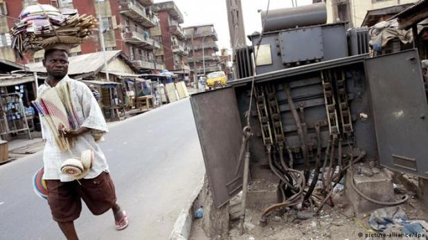 A man walks past a broken electricity transformer in Lagos, Nigeria