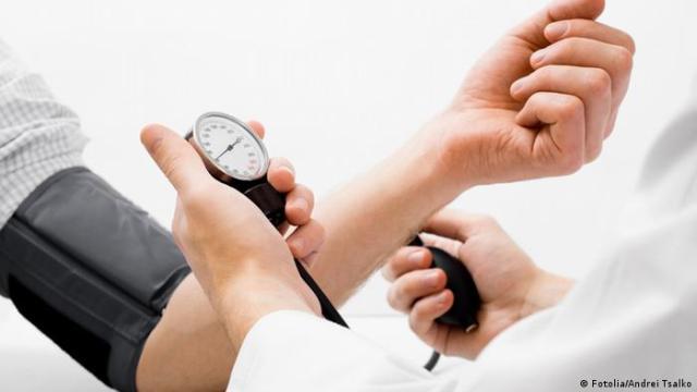 Arzt misst Blutdruck am Arm eines Patienten