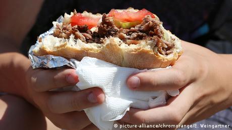 Hands hold a döner kebab sandwich (picture-alliance / chromorange / E. Weingartner)