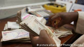 A man holds bundles of naira, Nigeria's currency