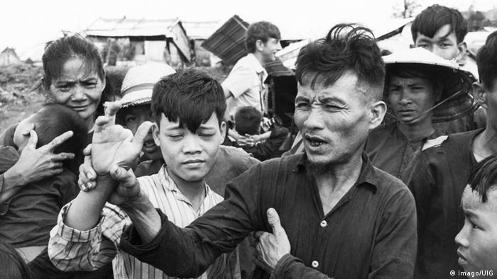 South Vietnamese peasant Do Chuc shows the mutilated hand of his son. The man and his child survived being shot in My Lai massacre