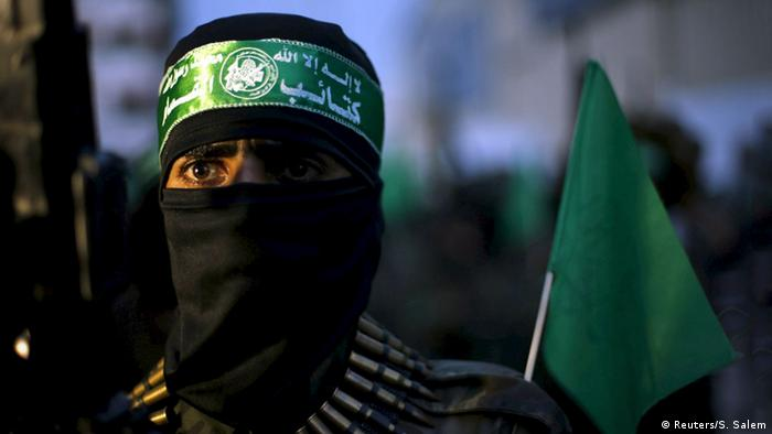 A man wearing a green headband with Fatah's symbol, his face covered and wearing bullets around his neck looks beyond the camera
