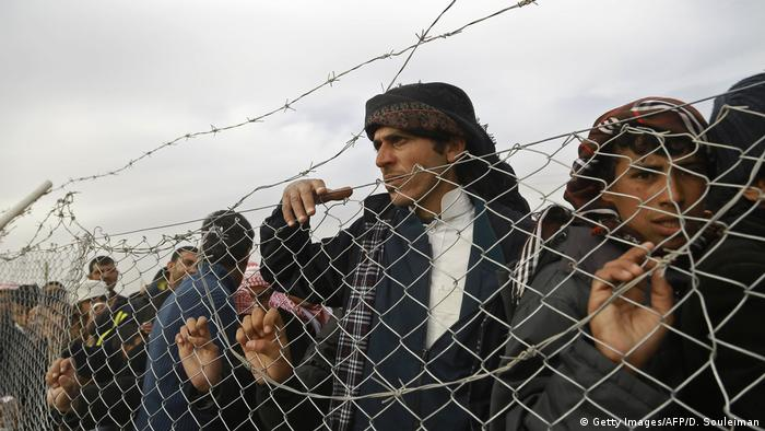 Migrants behind a wire fence (Getty Images/AFP/D. Souleiman)