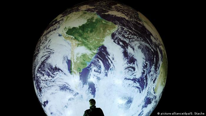 Mann vor Globus Ballon Symbolbild Klimawandel (picture-alliance/dpa/S. Stache)