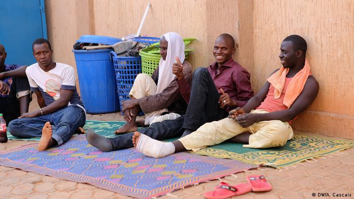 African refugees in Niger sit on the floor waiting for an opportunity to travel further to Europe