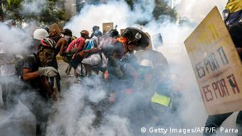 Demonstrators protect themselves from tear gas during clashes with riot police during a protest against the Maduro government in Caracas, May 20. AFP PHOTO / FEDERICO PARRA