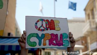 A demonstrator holds up a sign for unification on the divided island of Cyprus