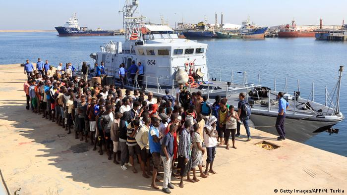 A group of African migrants standing on the dock after disembarking from the shiop that rescued them