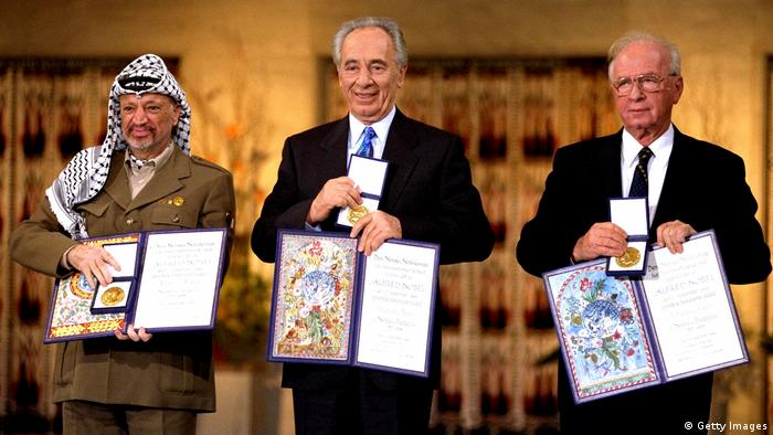 Yasser Arafat, Yitzhak Rabin and Shimon Peres hold up their Nobel Peace Prize medallions at a ceremoney in Oslo Norway in 1994
