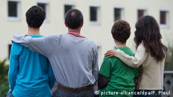 A family stands with its back to the camera and arms around one another(picture-alliance/dpa/P. Pleul)