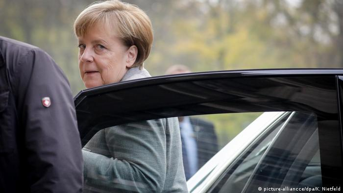 Angela Merkel looks over her shoulder while stepping out of a car (picture-alliancce/dpa/K. Nietfeld)