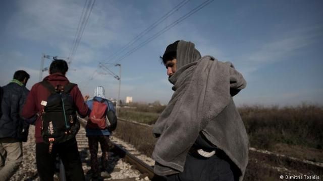 A group of refugees are walking on railway tracks