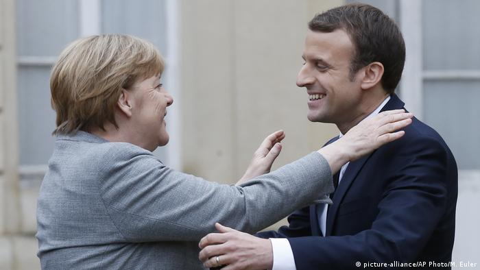 Angela Merkel and Emmanuel Macron embrace each other