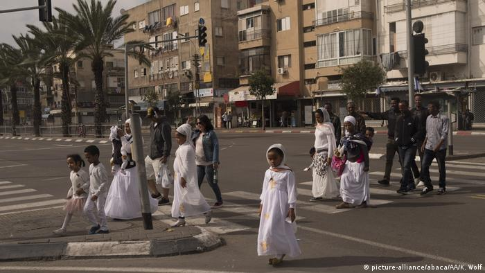 A group of African men, women and children cross a street in Tel Aviv
