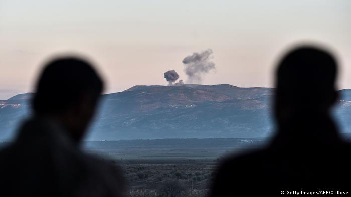 People look on as smoke rises on the Syrian side of the border in Hassa, near Hatay, southern Turkey, on January 28, 2018, as Turkish jet fighters hit People's Protection Units (YPG) positions. (Getty Images/AFP/O. Kose)