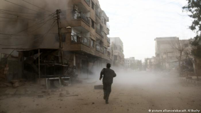 A man runs away from the scene after Assad Regime carried out an airstrike over Arbin town of the Eastern Ghouta region