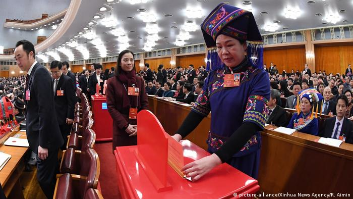 A deputy to the 13th National People's Congress (NPC) casts her ballot on a draft amendment to the country's Constitution at the third plenary meeting of the first session of the 13th NPC in Beijing