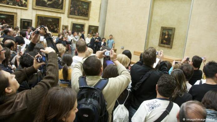 Menschen beobachten und fotografieren die Mona Lisa.