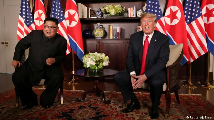 U.S. President Donald Trump sits next to North Korea's leader Kim Jong Un before their bilateral meeting at the Capella Hotel