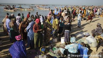 Fishmongers and customers congregate on the beach, with fishing canoes in the waters behind them (Imago/robertharding)