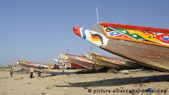 A row of colorful wooden fishing canoes docked on the beach. (picture-alliance/robertharding)